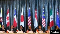 Perwakilan Perdagangan AS Michael Froman (tengah) diapit Menteri Ekonomi Jepang Akira Amari (tengah kiri) dan Menteri Perdagangan Singapore Lim Hng Kiang (tengah kanan), berada di atnara para Menteri Perdagangan Kanada, Peru, Malaysia dan Meksiko dalam konferensi pers yang diselengarakan di hari terakhir konferensi empat hari Konferensi Tingkat Menteri untuk Kerjasama Trans-Pasifik (TPP) di Singapura (25/2).