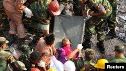 Tentara Bangladesh dan tim SAR saat menemukan seorang perempuan dalam keadaan selamat di antara reruntuhan gedung di Savar (10/5). Pencarian korban akan dihentikan Selasa 14/5.