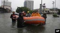 Lực lượng cứu hộ sử dụng thuyền cao su để di chuyển cư dân tại một khu vực bị ngập lụt ở thành phố Quezon, phía bắc Manila, ngày 7/8/2012