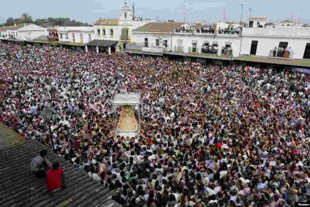 Pilgrims crowd around the Virgin of El Rocio during a procession around the shrine of El Rocio in Almonte, southern Spain.
