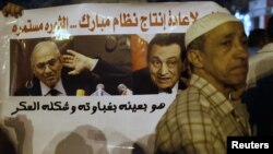 With a sign that reads 'No to restoring the former Mubarak regime,' in the background, protesters demonstrate against the results of the first round of Egypt's presidential elections at Tahrir Square in Cairo June 1, 2012.