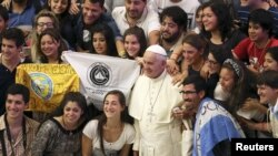 Pope Francis (C) poses for a picture with Argentinian youths during his Wednesday general audience in Paul VI hall at the Vatican, August 19, 2015.