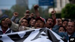 Protesters shout as they protest during a massive march in Mexico City, Thursday, Nov. 20, 2014.