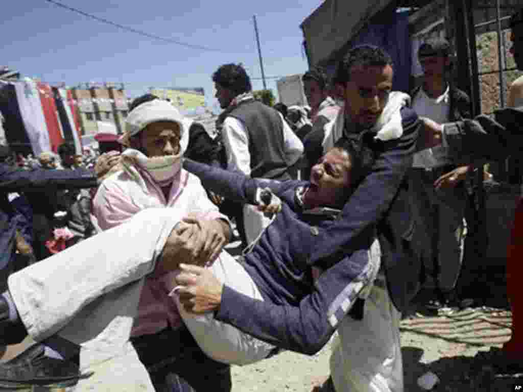 Anti-government protesters carry a protester wounded in October in clashes with security forces. (AP)