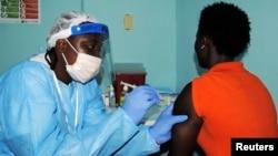 Nhân viên y tế tiêm vắcxin thử nghiệm cho một người phụ nữ ở Monrovia.