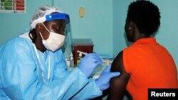 Un trabajador de la salud inyecta la vacuna a una voluntaria en Liberia.