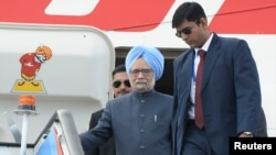 Indian Prime Minister Manmohan Singh (front L) walks down the stairs as he arrives a day before the G20 Summit in St. Petersburg, Sept. 4, 2013.