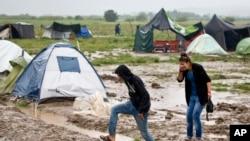 Un couple se déplace à travers une partie inondée du camp de migrants en Idomeni, Grèce, 21 mai 2016.