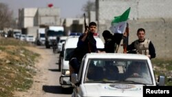FILE - Free Syrian Army fighters head a convoy of vehicles carrying humanitarian supplies as they enter Damascus, March 20, 2014.