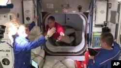Astronaut Mike Hopkins (tengah), disambut oleh astronaut Kate Rubins (kiri) saat ia memasuki Stasiun Luar Angkasa Internasional (ISS) dari ruang depan antara kapsul SpaceX Dragon dan ISS, Selasa pagi, 17 November 2020. (NASA TV via AP)