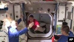 Phi hành gia Kate Rubins ở trạm ISS (áo xanh) chào đón phi hành gia Mike Hopkins (áo đỏ) từ tàu SpaceX Dragon, ngày 17/11/2020.