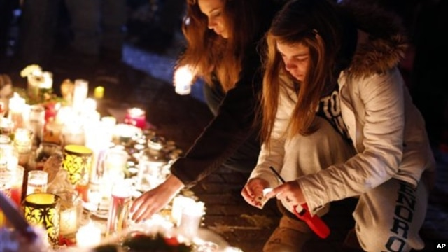 Visitors light candles at a memorial to shooting victims, Monday, Dec. 17, 2012, in Newtown, Conn.