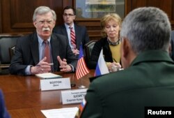 Russia's Defense Minister Sergei Shoigu, back to camera, meets with U.S. national security adviser John Bolton in Moscow, Oct. 23, 2018.