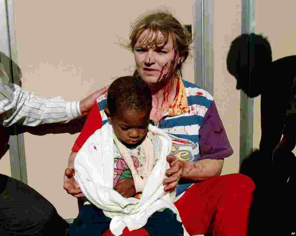Foto tanggal 19 April 1995 ini menunjukkan seorang perempuan yang terluka menggendong anak kecil setelah ledakan yang menghancurkan sebagian besar gedung Federal di tengah kota Oklahoma City.