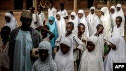Un groupe d'étudiants peuls fait la queue sur les terrains de l'école avant le début des cours de la journée à l'école nomade Wuro Fulbe de la réserve de Kacha Grazing pour peuple Peul, État de Kaduna, au Nigeria, le 19 avril 2019.