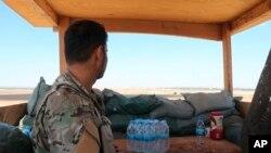 叙利亚民主力量的一名战士在叙利亚叙利亚-土耳其边境的塔尔艾卜耶德镇美军基地内站岗(2019年10月7日)。