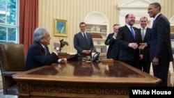 El presidente Barack Obama sonríe al ver al presidente de Chile, Sebastián Piñera sentado en su sillón presidencial.