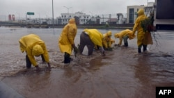 Municipal workers collect branches from a flooded street during Hurricane Patricia, in Manzanillo, Colima state, Mexico, Oct. 23, 2015.