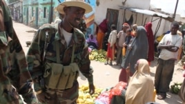 Women sell fruit at a market in Bala'ad, Somalia on July 3, 2012, as soldiers stand guard. (VOA/M. Yusuf)