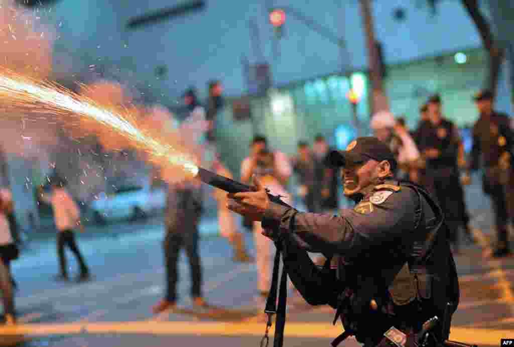 Cảnh sát chống bạo loạn bắn hơi cay vào những người biểu tình bạo động, khi xô xát xảy ra tiếp theo sau cuộc tuần hành của công nhân ở Rio de Janeiro, Brazil, vào ngày được gọi là ngày hành động, do các công đoàn lớn kêu gọi thực hiện để gây sức ép đòi cải thiện điều kiện làm việc