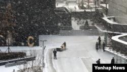 아침부터 눈이 내린 26일 서울 코엑스에서 직원들이 야외 바닥의 눈을 치우고 있다.