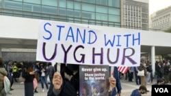 集會人士手持標語,與維吾爾族人同行。(攝影: 美國之音湯惠芸)