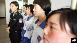 一位女警官站在中國東北一個勞教營的女性囚犯旁(資料照片)