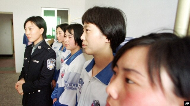 A female police officer is seen standing with women in a re-education camp in northeast China in this May 22, 2001, file photo.