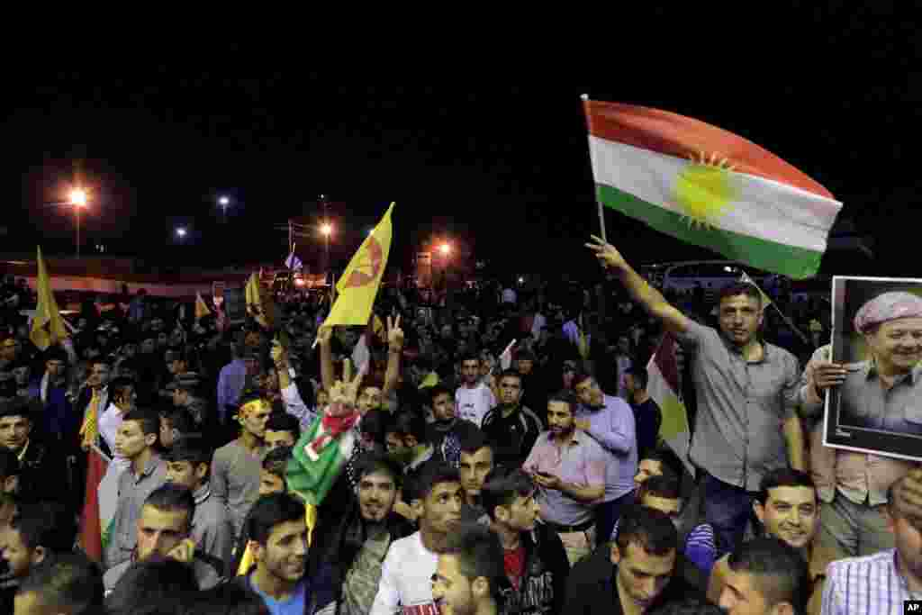 Thousands of supporters of Kurdish Peshmerga forces gather to celebrate as they wait for the troops to cross the border into Turkey en route to Kobani, at the Ibrahim Khalil border crossing, in the Northern Kurdish Region of Iraq, Oct. 29, 2014.