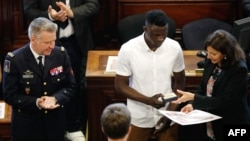 """Malian migrant Mamoudou """"Spider-Man"""" Gassama, center, is awarded Paris' Grand Vermeil medal by mayor Anne Hidalgo as the chief of the Paris' fire Brigade General Jean-Claude Gallet, left, applauds at the city council room in Paris, June 4, 2018."""