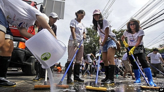 A Thai volunteer, left, pours detergent as others sweep a road during a cleaning drive after flood waters receded in Bangkok, Thailand, November 20, 2011.