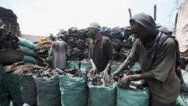 Somali businessmen arrange charcoal inside bags along a street near the main Baraka market in Mogadishu, March 27, 2012.