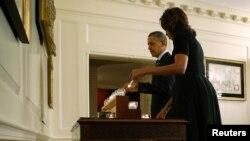 Presiden AS Barack Obama (kiri) dan ibu negara Michelle Obama menyalakan lilin dan mengheningkan cipta sejenak di Gedung Putih, Sabtu (14/12) untuk mengenang para korban tragedi penembakan di SD Sandy Hook setahun yang lalu.