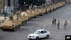 FILE - Egyptian army soldiers take their positions on top and next to their armored vehicles to guard an entrance of Tahrir Square, in Cairo, August 2013.