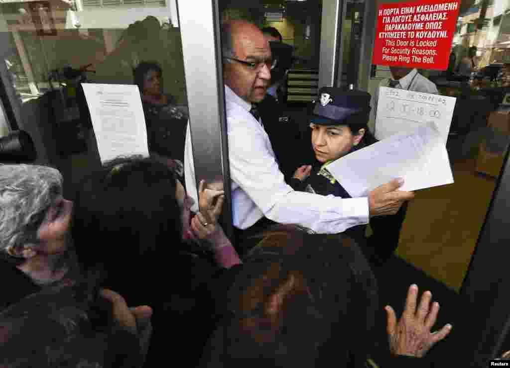 Nhân viên Ngân hàng Laiki ở Nicosia giúp một cảnh sát viên chen qua những người gửi tiền để lọt vào bên trong.