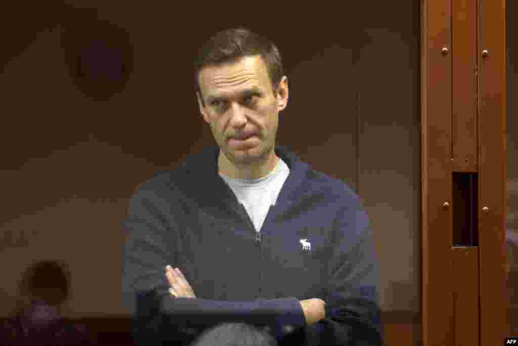 Russian opposition leader Alexei Navalny, charged with defaming a World War II veteran, stands inside a glass cell during a court hearing in Moscow, in this handout picture provided by the Babushkinsky district court.