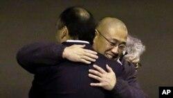 Ông Kenneth Bae (giữa), người đã bị giam cầm ở Bắc Triều Tiên từ năm 2012, đến khu căn cứ liên hợp Lewis-McChord ngày 8 tháng 11 năm 2014 sau khi được trả tự do trong một nhiệm vụ tối mật.