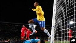 Luis Fabiano wa Brazil akiruka juu ya golikipa wa Korea Kaskazinii Myong Guk, baada ya mwenzake Maicon kupachika bao la kwanza. (Picha AP /Andre Penner)