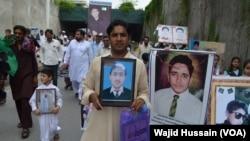Warga Pakistan membawa gambar para korban tewas serangan atas sekolah di Peshawar tahun 2014 (foto: dok).