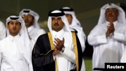 Qatar's Crown Prince Sheikh Tamim bin Hamad al-Thani (C) attends a soccer match at al-Sadd Stadium in Doha, May 4, 2013.