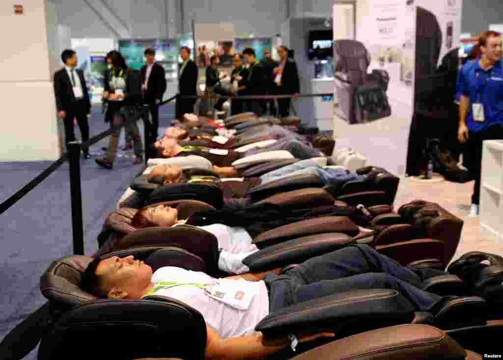 بازددکنندگان نمایشگاه کالاهای الکترونیکی در لاس وگاس، صندلی ماساژ ماج ۷ پاناسونیک را امتحان می کنند.