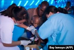 Petugas kesehatan mengambil sampel darah seorang anak Papua di rumah sakit sementara yang menangani pasien campak dan gizi buruk di Agats, ibu kota Kabupaten Asmat pada 25 Januari 2018. (Foto: AFP/Bay Ismoyo)