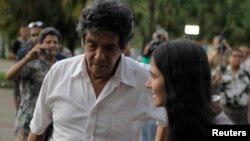 FILE - Cuba's best-known dissident, blogger Yoani Sanchez, walks with her husband Reinaldo Escobar outside Havana's Jose Marti International Airport, May 30, 2013.