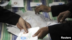 Officials count ballots after polls closed in Zagazig, about 62.5 km northeast of Cairo on Dec.15, 2012.