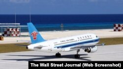 This handout picture from China's official Xinhua News Agency shows a China Southern Airlines civilian plane landing at a newly-built airstrip on an island at Fiery Cross Reef, in the South China Sea, on Jan. 6, 2016.