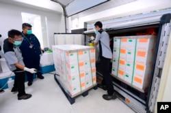Pekerja menyemprot disinfektan pada kotak vaksin virus Sinovac, yang tiba di fasilitas Bio Farma, Bandung (dok: Istana Kepresidenan Indonesia/AP)