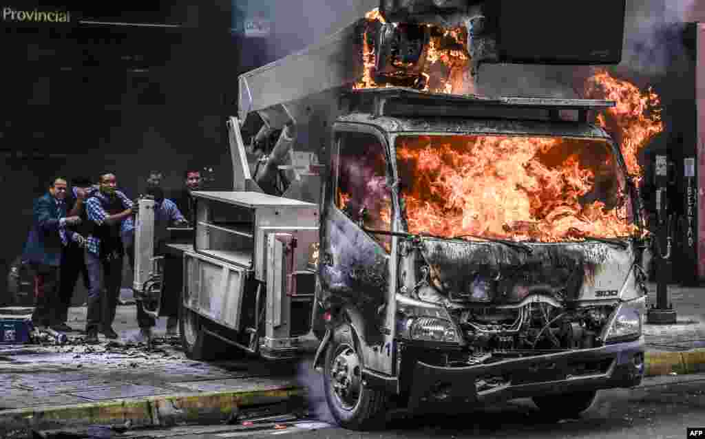 Supreme Justice Court (TSJ) workers push a truck set ablaze by protesters away from the premises during clashes between riot police and opposition activists to protest against the government of President Nicolas Maduro in Caracas, Venezuela, June 7, 2017.