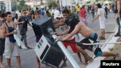 Người biểu tình Brazil phá đổ một cột đèn giao thông trong cuộc đụng độ với cảnh sát chống bạo động gần Estadio Castelao, Fortaleza, ngày 19/6/2013.