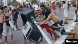 19일 브라질 포탈레자에서 대중교통 요금 인상과 정부 체제에 반대하는 시위대가 교통신호등을 끌어내리고 있다.