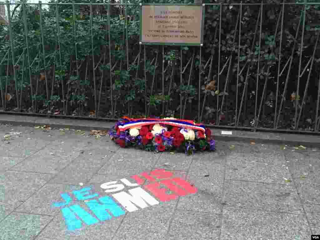 """این پلاک برای احمد مرابه، پلیس مسلمانی است که در ماجرای حمله به نشریه شارلی ابدو کشته شد. علاوه بر پلاک، روی زمین با رنگ پرچم فرانسه نوشته شده """"من احمد هستم"""". شعاری که برخی بعد از حملات ژانویه در کنار شعار """"من شارلی هستم"""" استفاده می کردند."""